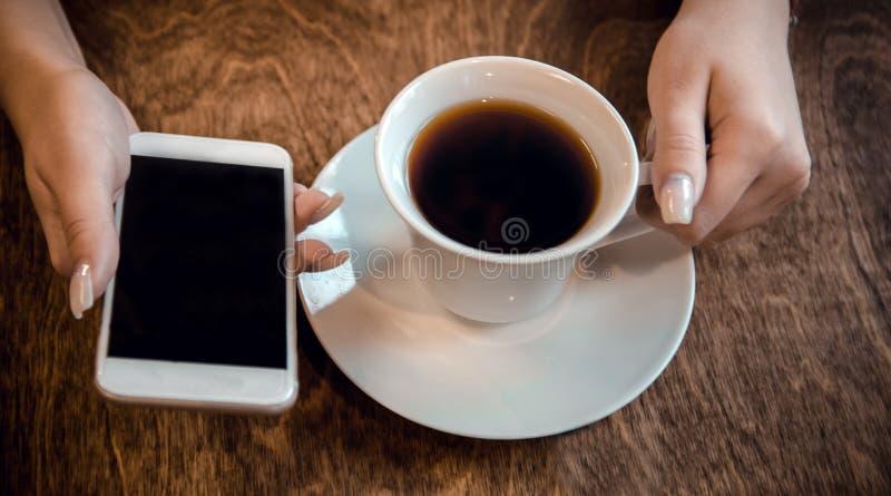 Het meisje zit in een koffie en houdt een kop thee en een telefoon in haar handen, wachtend op een vraag stock fotografie