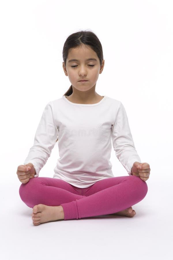 Het meisje zit in een Positie van Lotus van de Yoga royalty-vrije stock fotografie