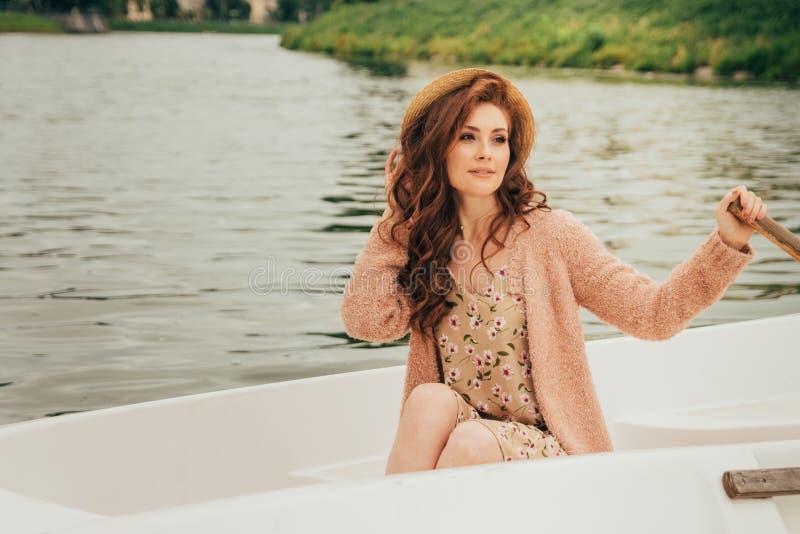 het meisje zit in een witte boot op de rivier royalty-vrije stock afbeelding