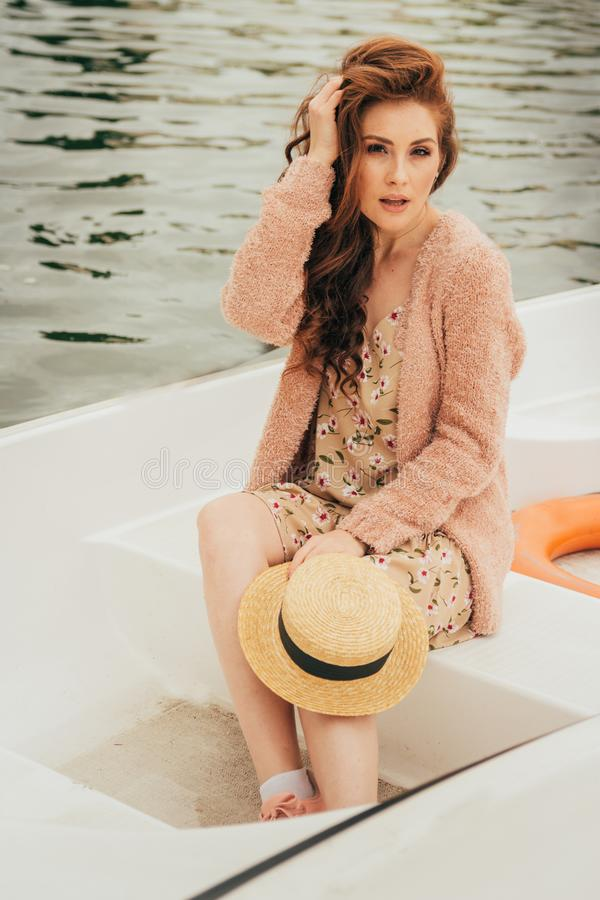 het meisje zit in een witte boot op de rivier in handen houdt een hoed van de zon stock fotografie