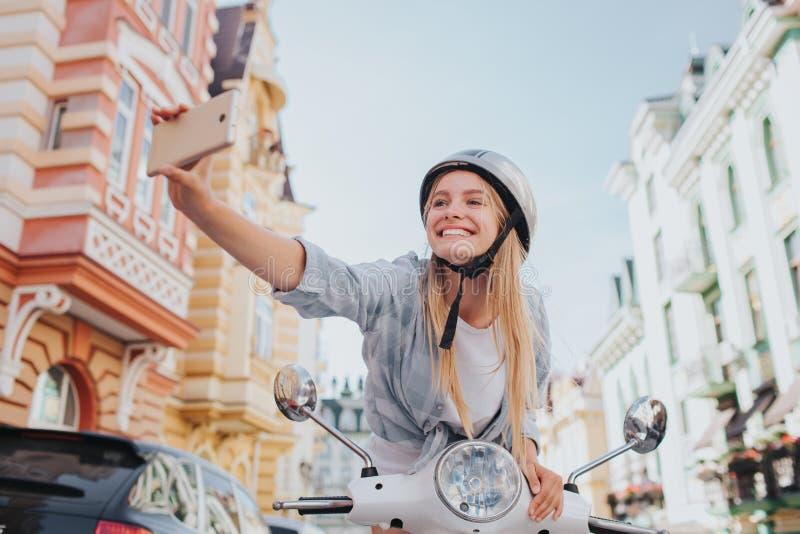Het meisje zit en leunt aan en motorfiets` s controle die selfie headling nemen Zij houdt telefoon in hand Het meisje is stock foto's