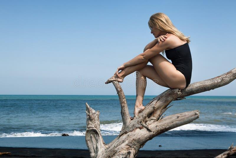 Het meisje zit en ontspant op boomtak, kijkt op zee stock afbeelding