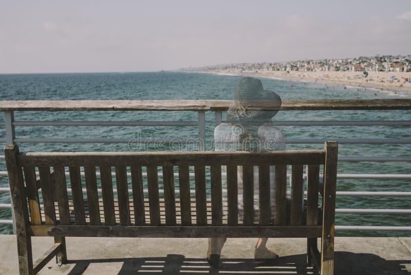 Het meisje zit en overweegt op een Bank met Oceaanmening stock fotografie