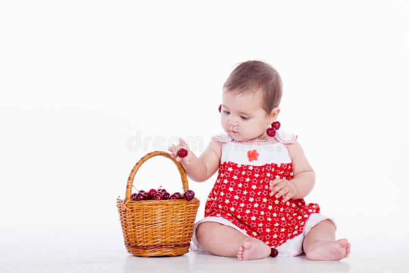 Het meisje zit met mand van kersen stock fotografie