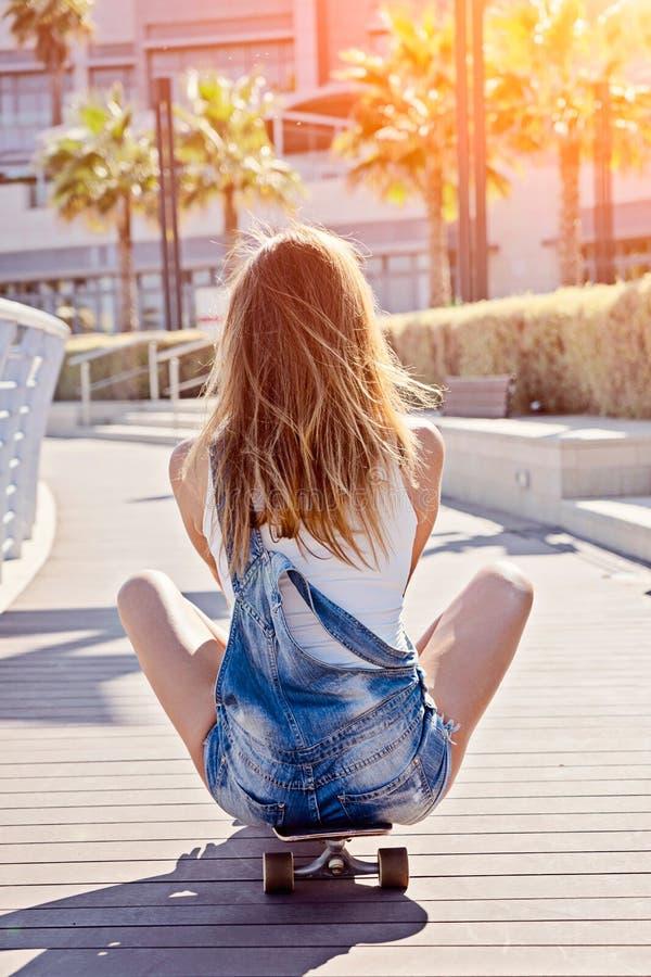 Het meisje zit met zijn rug op longboard stock foto