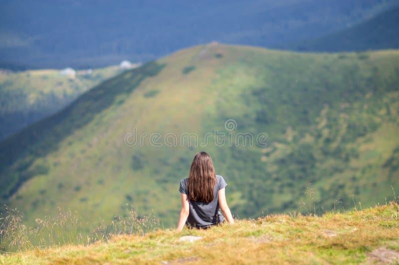 Het meisje zit op de rand van de berg stock afbeelding