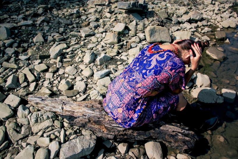 Het meisje zit op de rotsen zich omdraait met haar terug naar de fotograaf stock fotografie