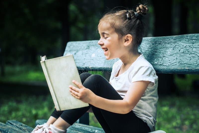 Het meisje zit op een bank en leest een boek stock afbeeldingen