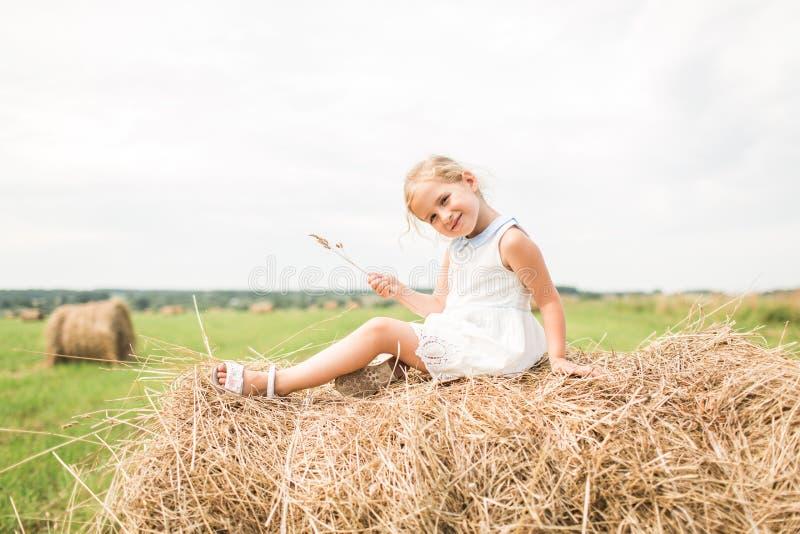 Het meisje zit op een hooiberg, een de zomerconcept stock foto