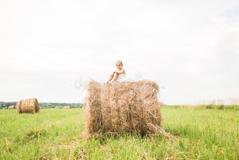 Het meisje zit op een hooiberg, een de zomerconcept stock foto's