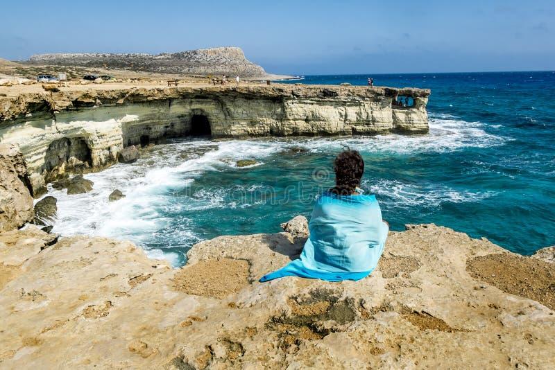Het meisje zit op een richel van rots boven het overzees bij Kaap Greco Cypru royalty-vrije stock fotografie