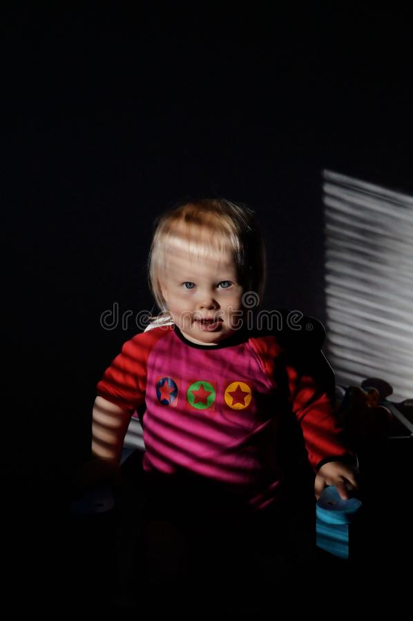 Het meisje zit op een stoel stock afbeelding