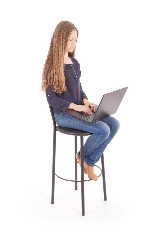 Het meisje zit op een stoel en een holding een laptop computer royalty-vrije stock afbeelding