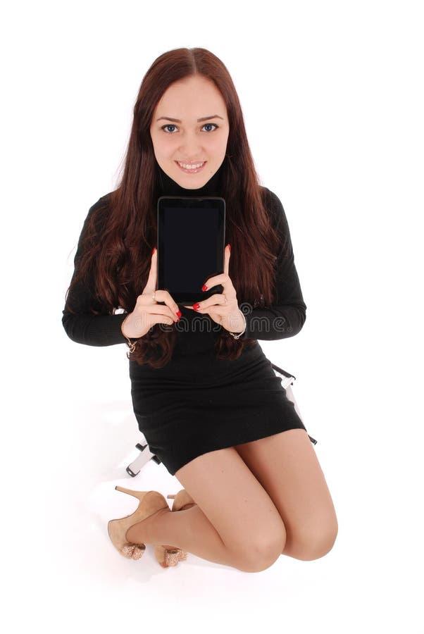Het meisje zit op een stoel en een holding een tabletcomputer royalty-vrije stock foto's