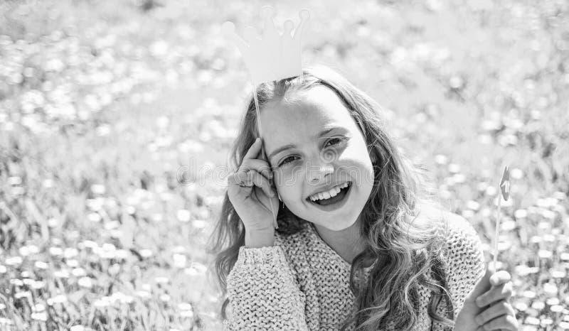 Het meisje zit op gras bij grassplot, groene achtergrond Het meisje op vrolijk gezicht besteedt in openlucht vrije tijd Prinsesco royalty-vrije stock foto's