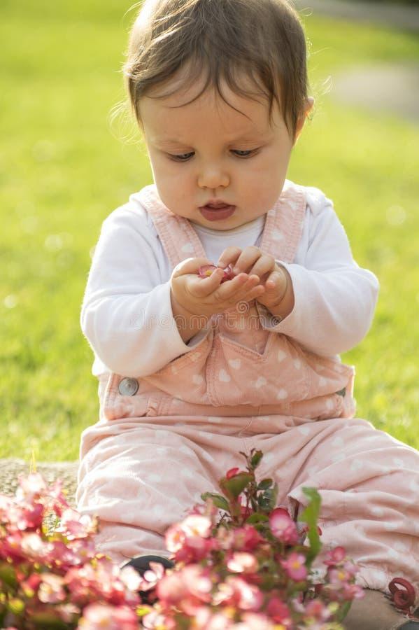 Het meisje zit op groene weide en speelt met bloemen royalty-vrije stock afbeeldingen