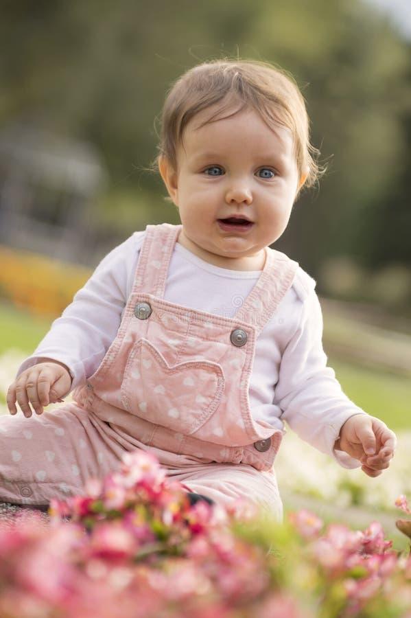 Het meisje zit op groene weide en speelt met bloemen stock afbeeldingen