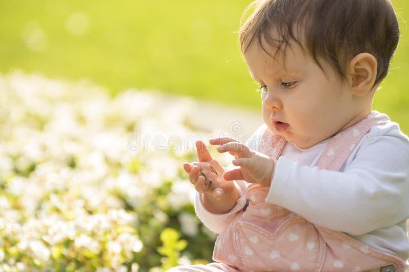 Het meisje zit op groene weide en speelt met bloemen stock fotografie