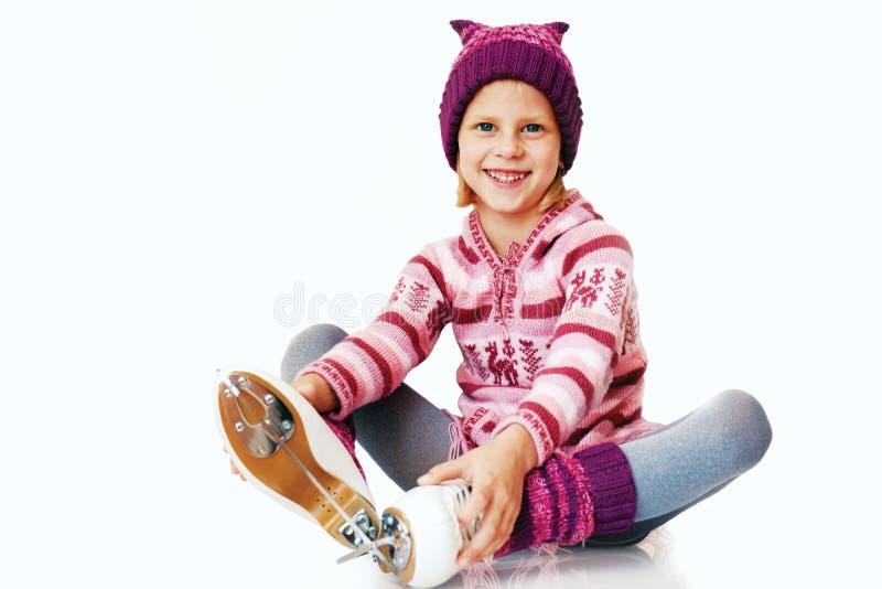 Het meisje zit op het ijs in ijs het schaatsen Geïsoleerd op witte bedelaars royalty-vrije stock foto