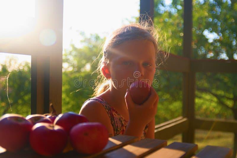 Het meisje zit op portiek in de zomer Het kleine meisje eet appelen Appelen op lijst Dromerig en romantisch beeld royalty-vrije stock afbeelding