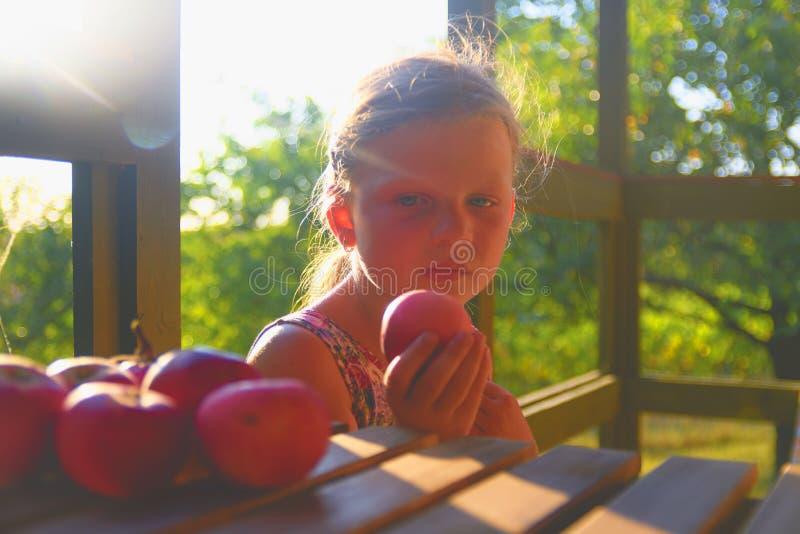 Het meisje zit op portiek in de zomer Het kleine meisje eet appelen Appelen op lijst Dromerig en romantisch beeld royalty-vrije stock fotografie