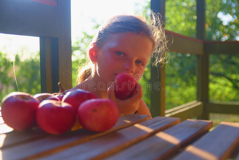 Het meisje zit op portiek in de zomer Het kleine meisje eet appelen Appelen op lijst Dromerig en romantisch beeld royalty-vrije stock foto