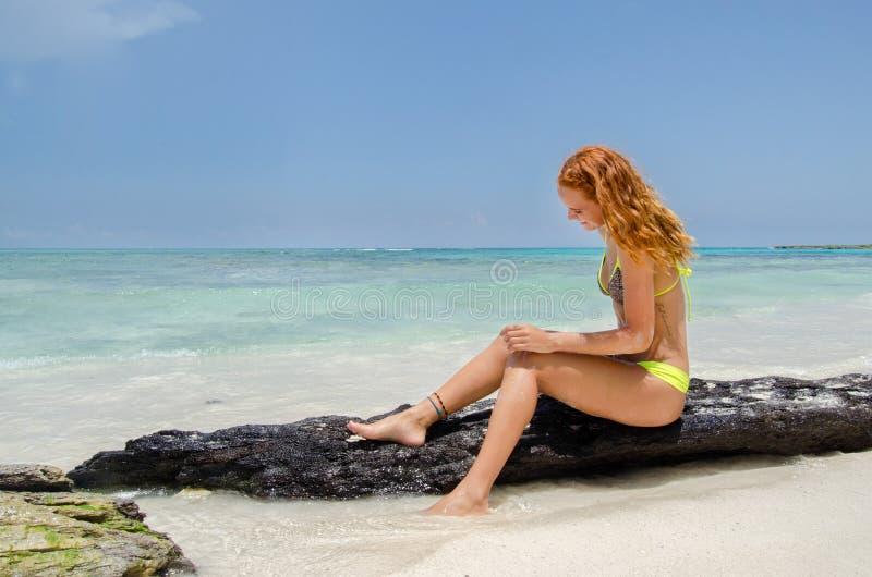 Het meisje zit op rots stock fotografie