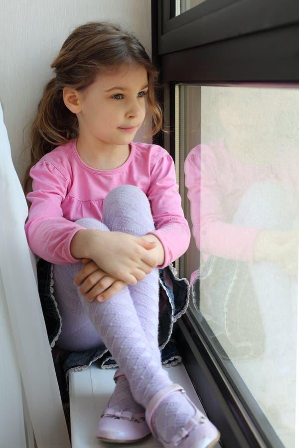 Het meisje zit op vensterbank en kijkt uit venster stock afbeeldingen