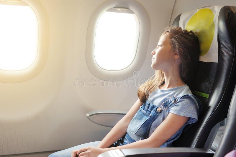 Het meisje zit in salon het vliegtuig stock afbeelding
