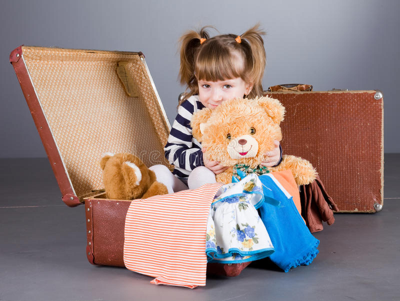 Het meisje zit vreugdevol in een oude koffer stock fotografie