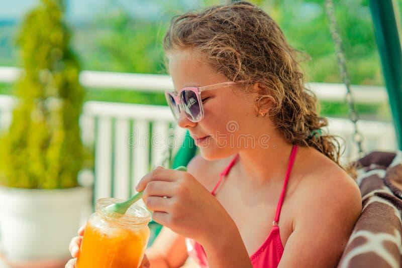 Het meisje zonnebaadt, rust op de schommeling, eet honing en drinkt een cocktail stock foto's