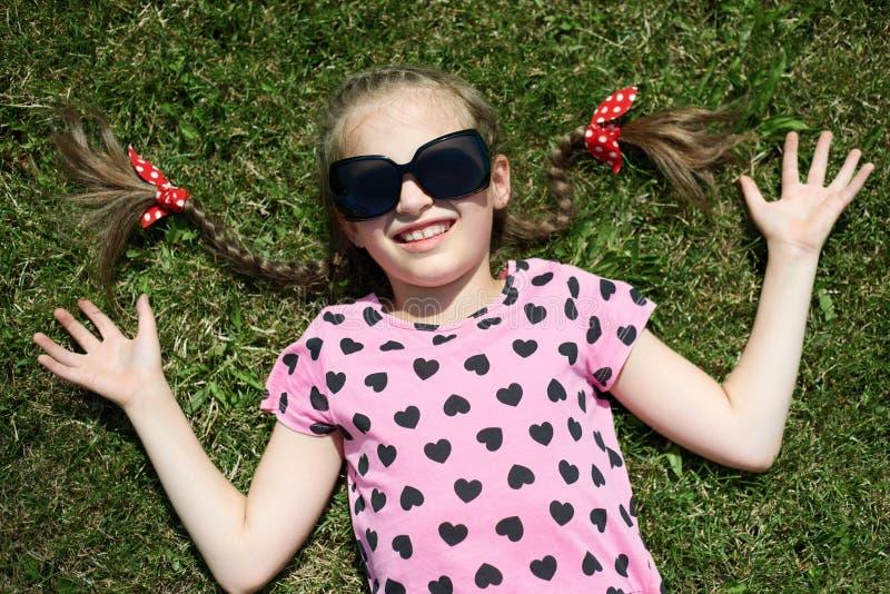 Het meisje in zonnebril ligt op groen gekleed gras, in roze kleren met harten, heldere zon, de zomer openlucht, hoogste mening royalty-vrije stock afbeelding