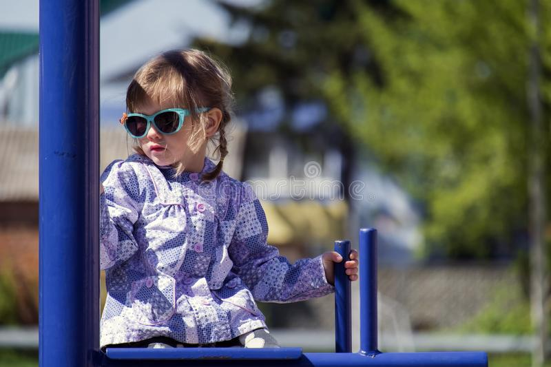 Het meisje in zonnebril zit op de dwarsbalk royalty-vrije stock fotografie