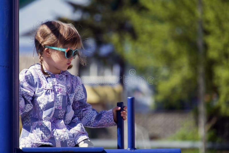 Het meisje in zonnebril zit op de dwarsbalk royalty-vrije stock foto's