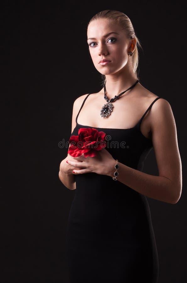 Het meisje in zwarte kleding met rood nam toe stock foto's