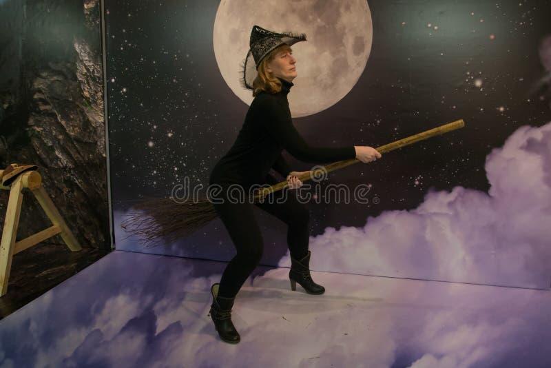 Het meisje in zwarte kleren en hoed schildert een heks af stock foto