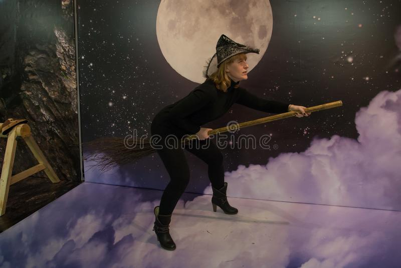 Het meisje in zwarte kleren en hoed schildert een heks af royalty-vrije stock afbeeldingen