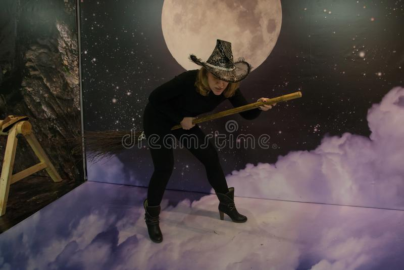Het meisje in zwarte kleren en hoed schildert een heks af stock foto's