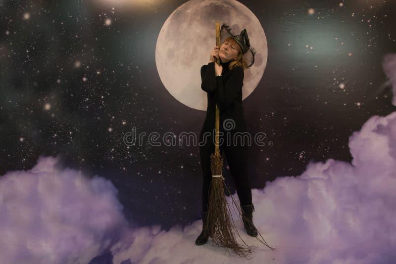 Het meisje in zwarte kleren en hoed schildert een heks af royalty-vrije stock fotografie