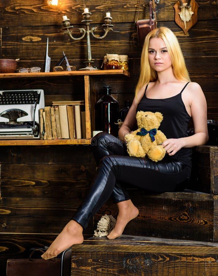 Het meisje in zwarte kleren houdt teddybeerstuk speelgoed in hand, houten binnenland op achtergrond Het dameblonde geniet van vri royalty-vrije stock afbeelding