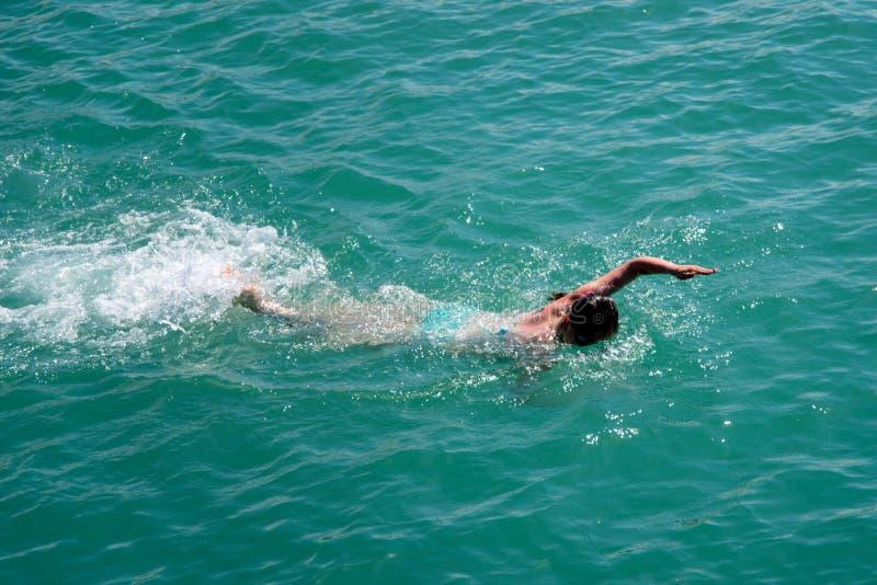 Het meisje zwemt vrij slag in het overzees stock foto