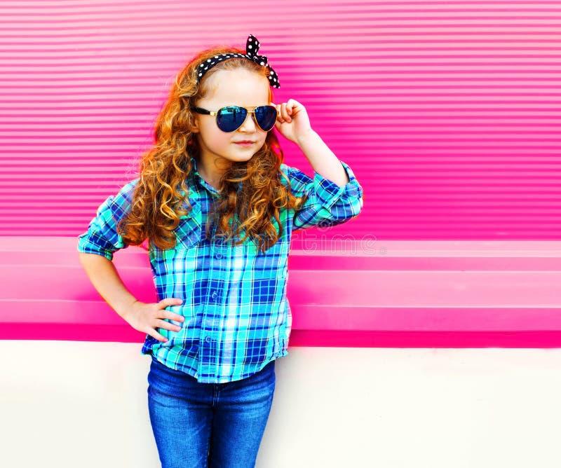 Het meisjekind van het manierportret in geruit overhemd, zonnebril die op kleurrijk roze stellen stock foto's