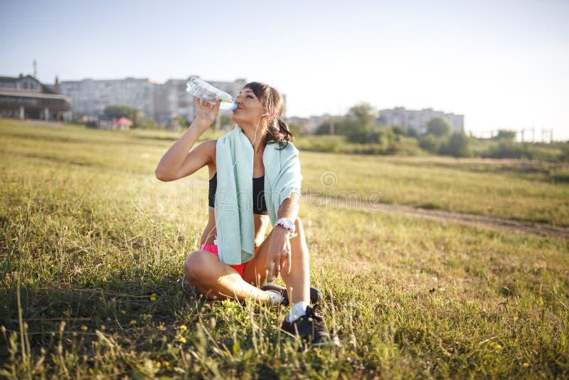 Het meisjes drinkwater van de sport na sport De zitting van het meisje op het gras Het voortbouwen op de achtergrond royalty-vrije stock foto