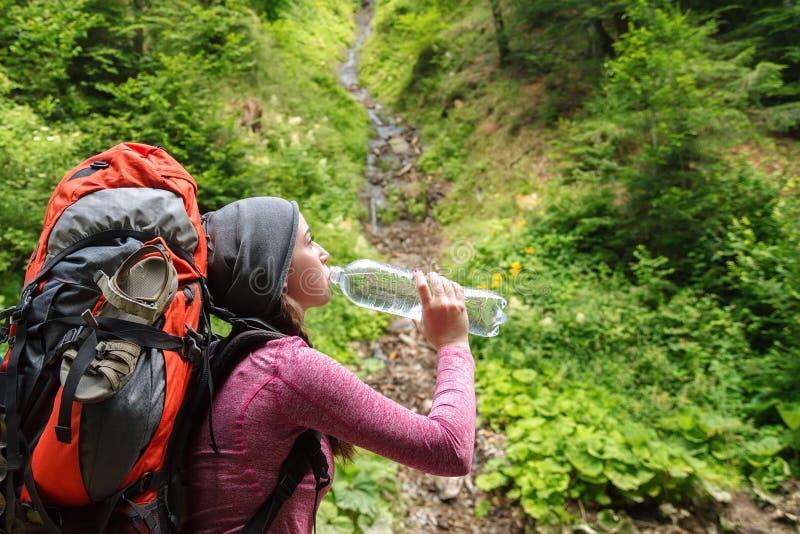 Het meisjes drinkwater van de wandelaar royalty-vrije stock foto's