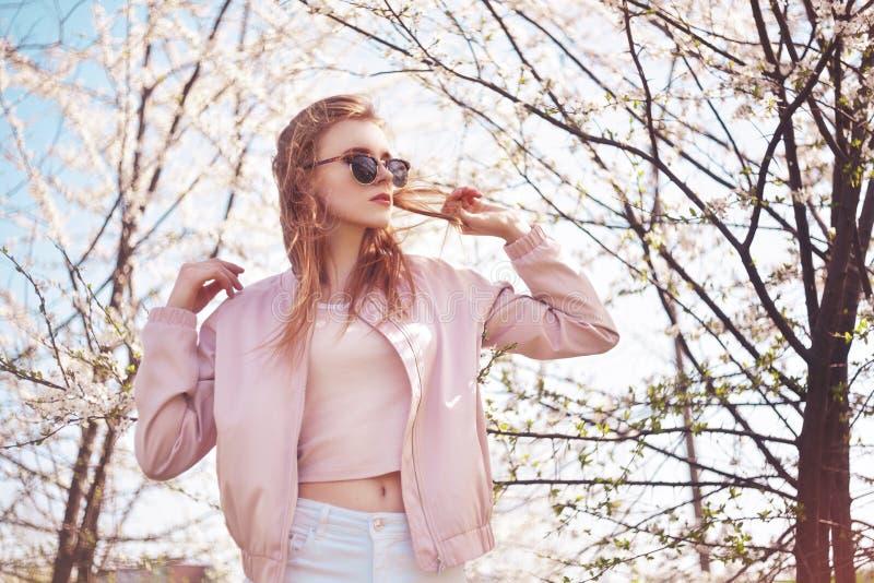 Het meisjes in openlucht portret van de de lentemanier in bloeiende bomen Schoonheids Romantische vrouw in bloemen in zonnebril S royalty-vrije stock afbeeldingen