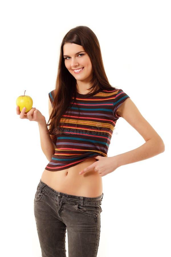 Het meisjes vrolijke slank van de tiener met appel stock foto