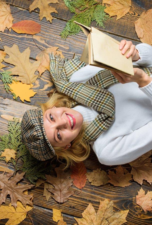 Het meisjesblonde legt houten achtergrond met bladeren Zij houdt detective van genre Vrouwendame in geruite hoed en gelezen sjaal royalty-vrije stock afbeeldingen