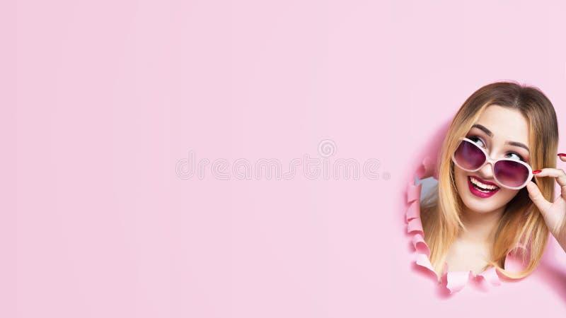 Het meisjeshoofd in kartongat, jonge vrouw hief haar zonnebril op die de zomervakantie plannen en over aanbieding van hete bons d royalty-vrije stock afbeeldingen