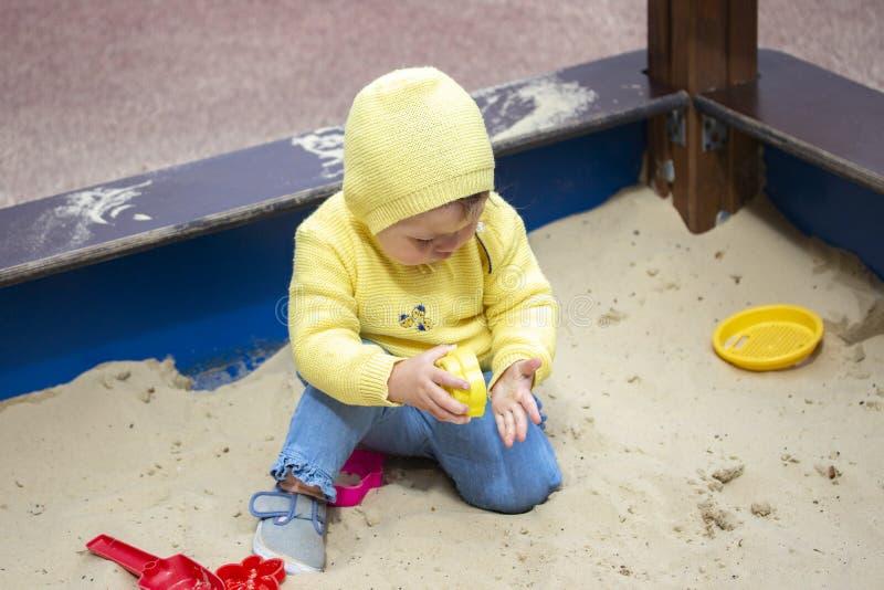 Het meisjesjongen van de kindbaby één éénjarige die op de speelplaats in de zandbak spelen Een kind in gele kleren zit in een zan royalty-vrije stock afbeelding
