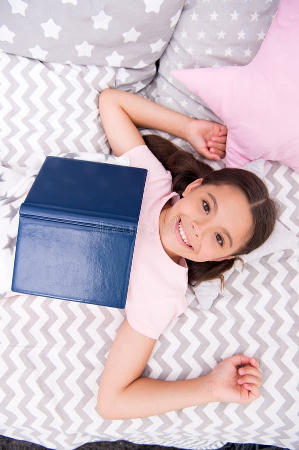 Het meisjeskind legt bed gelezen boek hoogste mening Het jonge geitje treft naar bed te gaan voorbereidingen Prettige tijd in com royalty-vrije stock afbeelding